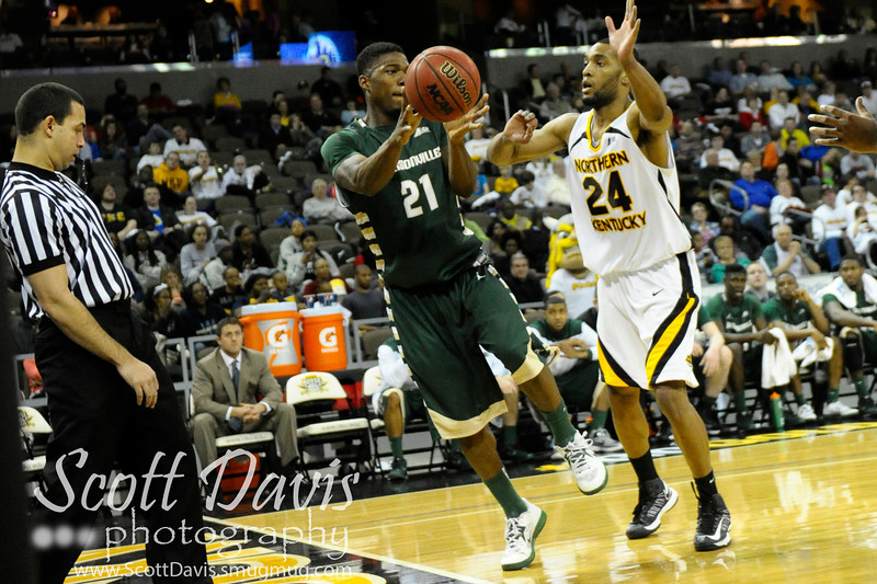 Jacksonville Dolphins guard Kieth McDougald #21 saves the ball over Northern Kentucky Norse guard Chad Jackson #24 during the college basketball game between Northern Kentucky Norse and  Jacksonville Dolphins .  Jacksonville Dolphins lead the Northern Kentucky Norse 30-29 at the half at The Bank of Kentucky Center in Highland Heights, Kentucky.