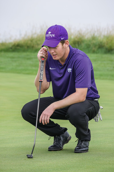 Jared Strathe, a freshman in business administration, concentrates on finding the perfect line before putting his golf ball towards the hole. Strathe focuses on polishing his short game skills before his practice round at Colbert Hills Country Club. (Brooke Barrett | Collegian Media Group)