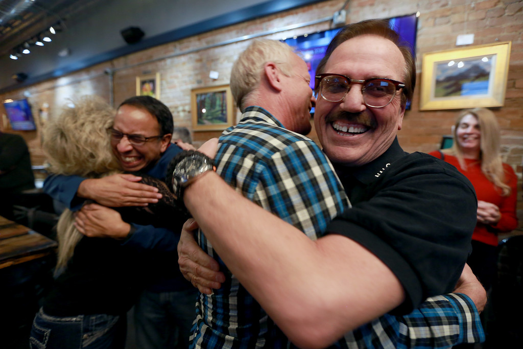 . Campaign manager Gil Barela hugs Larimer County Commissioner Steve Johnson after election results show ballot issue 1A ahead by a wide margin on as Matt Villalovos hugs Darla Barela too on Tuesday, Nov. 6, 2018 at Loveland TapHouse in Loveland, Colo.