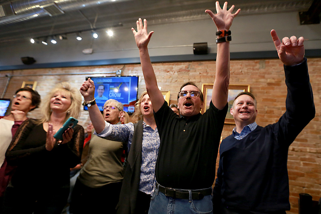 . Campaign manager Gil Barela, center right, reacts as election results show ballot issue 1A ahead by a wide margin on Tuesday Nov. 6, 2018 in Loveland Colo. at the Loveland TapHouse. Celebrating with him from left are Allison Hade, Darla Barela, Diann Rice, Jody Shadduck-McNally and Michael Allen. Photo by Taelyn Livingston/ Loveland Reporter-Herald