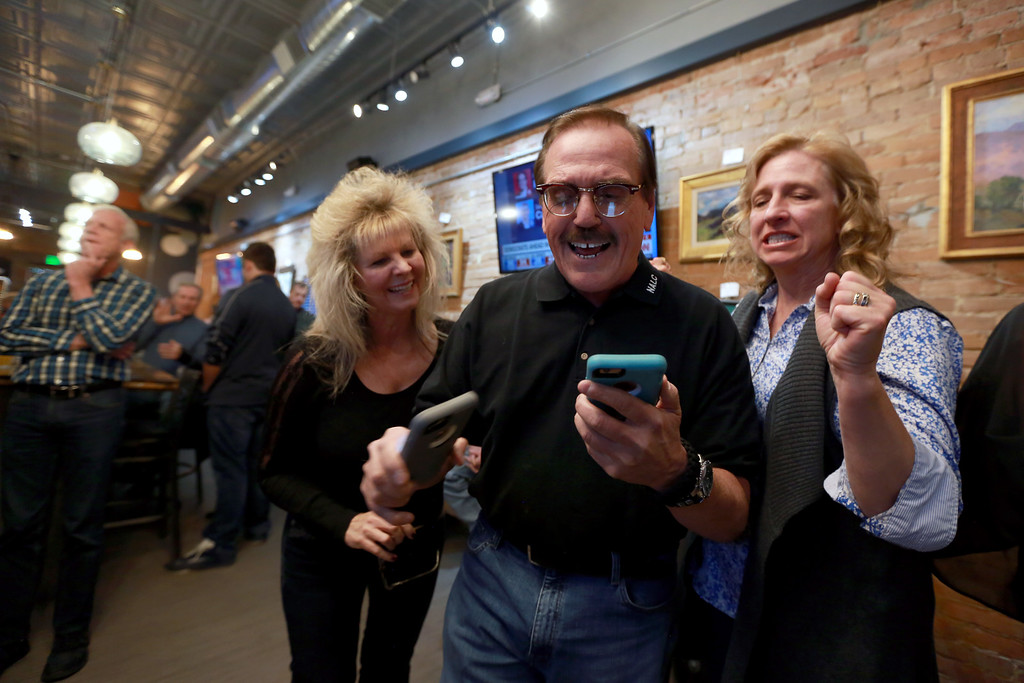 . Campaign manager Gil Barela, center, reacts with his wife, left, Darla Barela and, right, Jody Shadduck-McNally as election results show ballot issue 1A ahead by a wide margin on Tuesday Nov. 6, 2018 in Loveland Colo. at the Loveland TapHouse. Photo by Taelyn Livingston/ Loveland Reporter-Herald