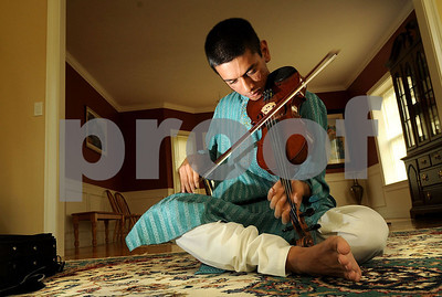 Seventeen-year-old Suhas Rao bows his violin cross legged while playing classical Indian music called carnatic violin.