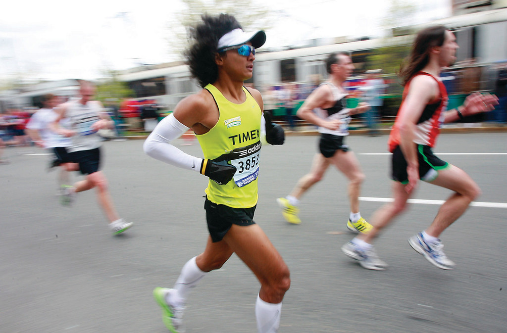 Rio B. De La Cruz of Marikina, Phillipines, runs through Brookline's Coolidge Corner in the 114th Boston Marathon.