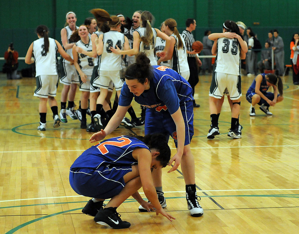 Newton South senior Chloe Rothman (14) consoles senior Kendall Burton (22) following their loss to Mansfield in the Division 1 South State tournament at Massasoit Community College, March 09, 2011.