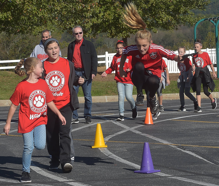 . PETE BANNAN-DIGITAL FIRST MEDIA   French Creek Elementary fifth grader,Kaydence Van Guilder right does a jump during the school\'s walk-a-thon on Oct. 18, the school PTA purchased each student and staff member a pedometer to encourage students as Chester County  worked to become the healthiest county in America.