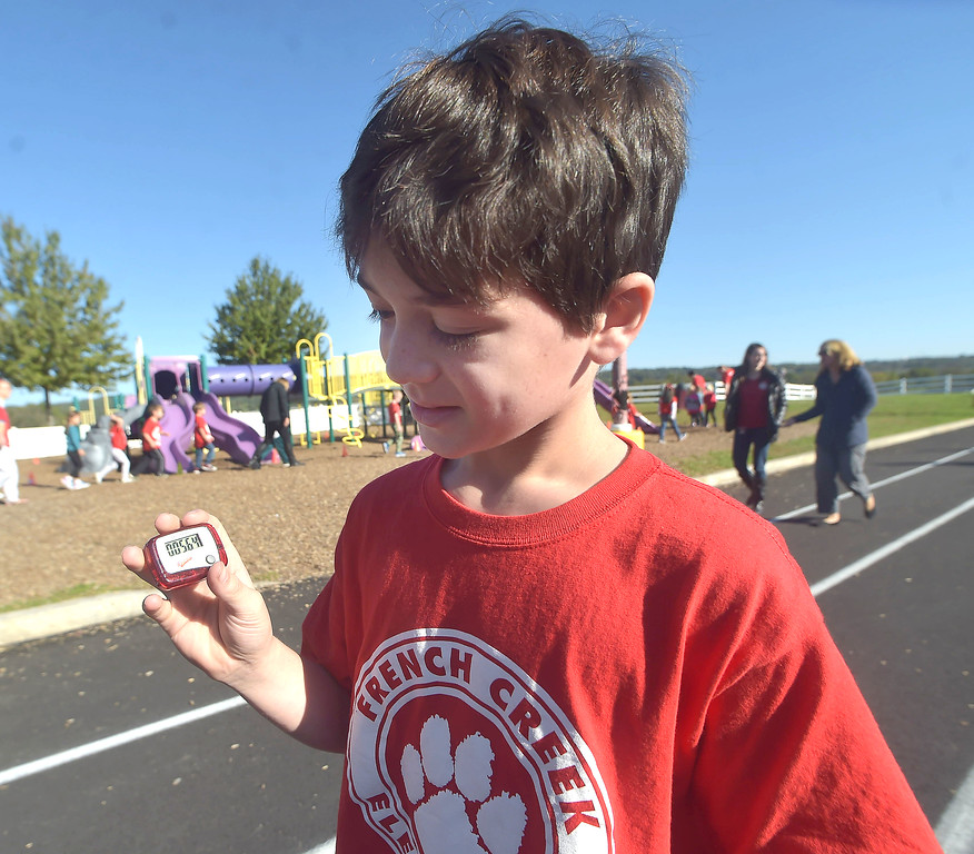 . PETE BANNAN-DIGITAL FIRST MEDIA   French Creek Elementary School,fifth grader, Tyler Freire check his pedometer during the school\'s walk-a-thon on Oct. 18, the school PTA purchased each student and staff member a pedometer to encourage students as Chester County  worked to become the healthiest county in America.