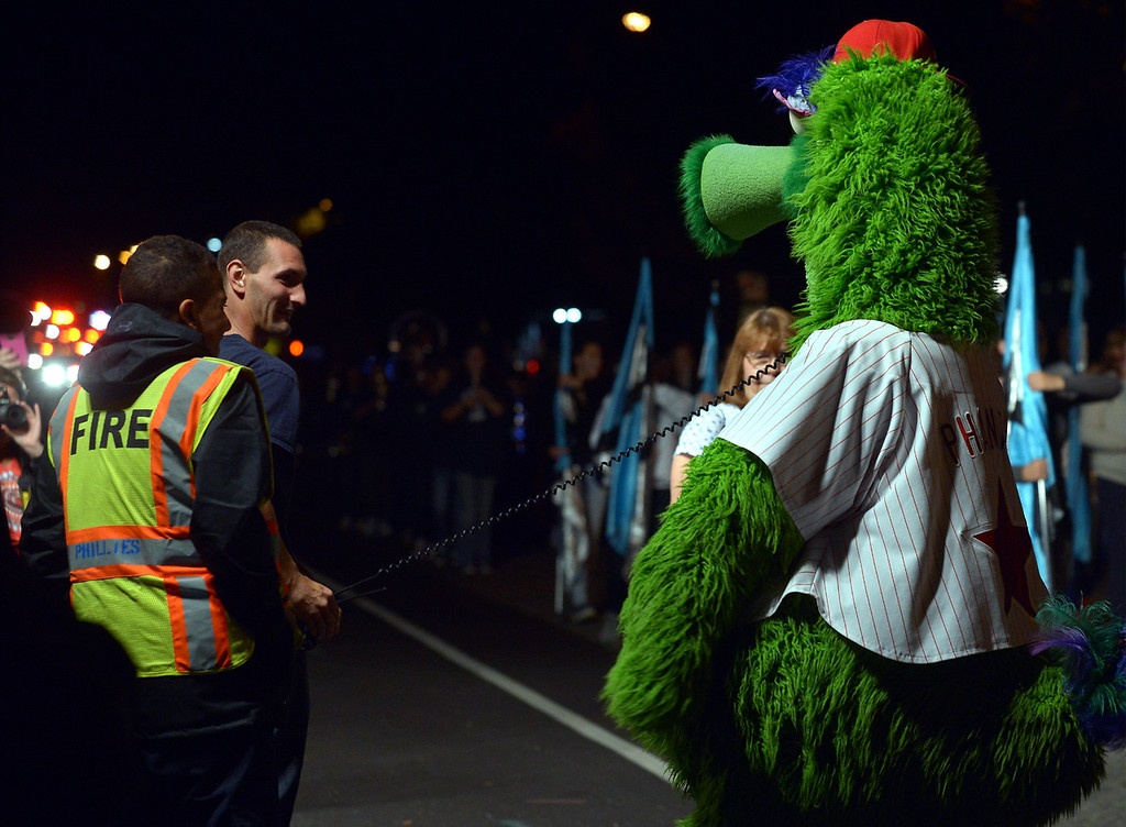 . The Phillie Phanatic tries to make off with a firefighter\'s radio during the Pottstown Halloween Parade Oct. 24, 2017. (Bob Raines--Digital First Media)