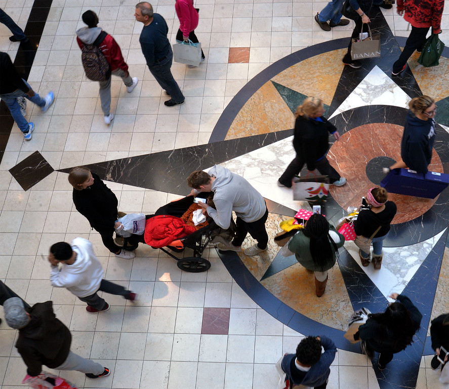 . A couple and their child pause as other shoppers swirl around them at King of Prussia Mall Nov. 24, 2017. (Bob Raines--Digital First Media)