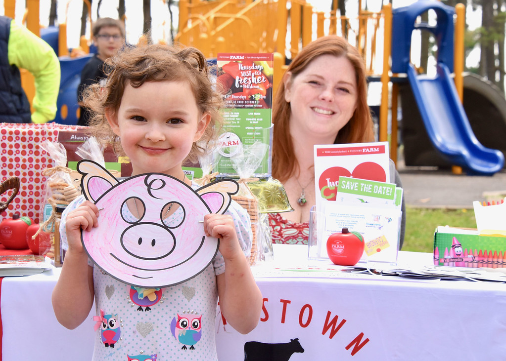 . Jesi Yost � For Digital First Media 6-year-old Clover Draves from Boyertown Elementary School, pictured with Audra Hammer Ross, a Pottstown Downtown Improvement District Authority volunteer, colored a pig mask at the Pottstown FARM (Farm and Regional Market) EarthFest table.
