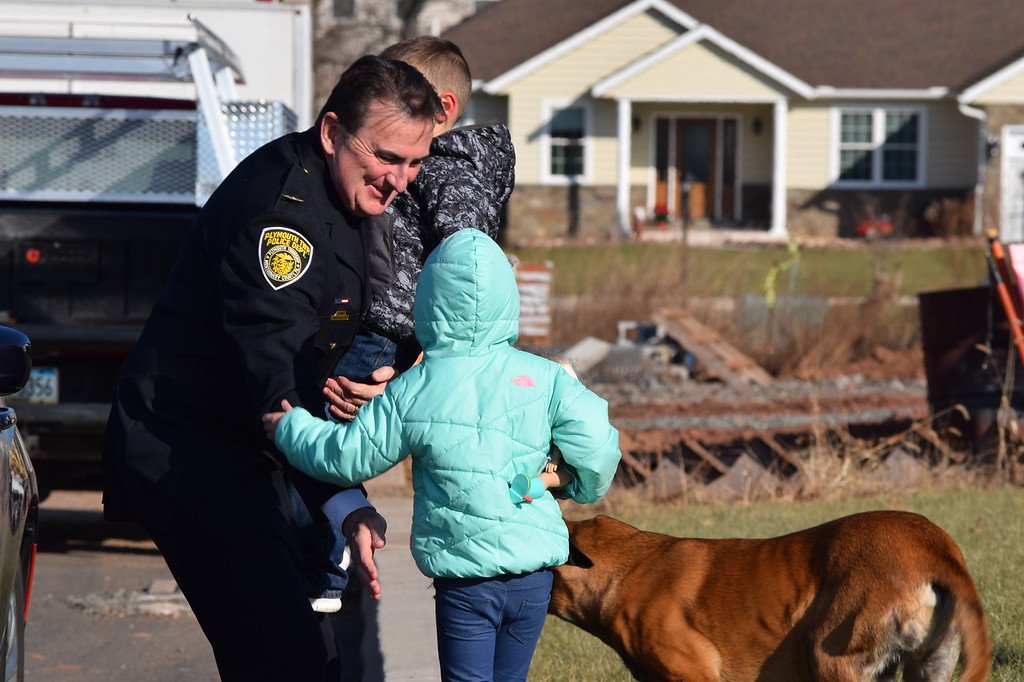 . Plymouth Township Police Chief Joseph Lawrence is greeted with hugs by Kadence and Brad Jr., the children of fallen Plymouth Township Police Office Brad Fox. The police department, along with several others made a special visit to the family for a holiday Meals on Wheels. Marian Dennis--Digital First media