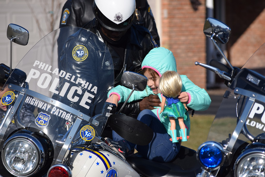 . Kadence Fox takes a seat on a police motorcycle parked outside the Fox home in Gilbertsvillle. Police officers stopped by to deliver a special Meals on Wheels box and visit with the family. Marian Dennis -- Digital First Media