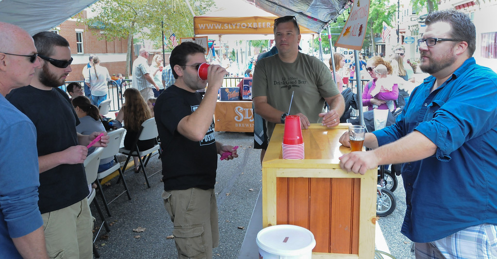 . John Strickler - The Mercury Armstrong Ale Brewing\'s Brian Todie and Dave Ruczhak were pouring craft ale at the beer tent during the Carousel of Flavor held Sunday on High Street in Pottstown.