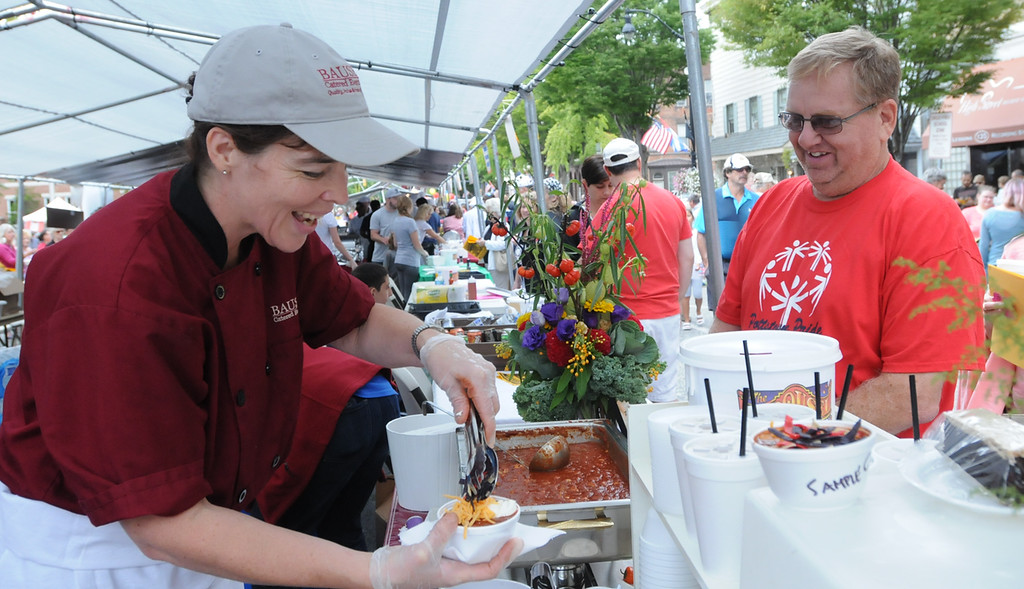 . John Strickler - The Mercury Erin Bause of Bause Catered Events dishes out a bowl of chili for Keith Nash at the Carousel of Flavor event.
