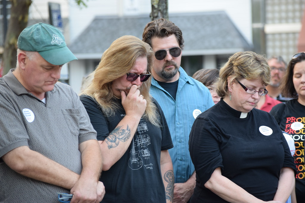 . Attendees at a vigil for Charlottesville that was held in Smith Family Plaza Thursday hang their heads in a moment of silence to remember the victims in Charlottesville. Marian Dennis -- Digital First Media
