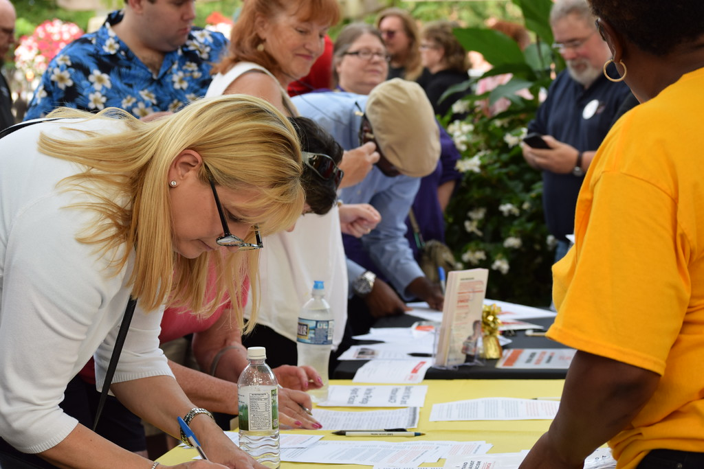 . As groups showed up for the vigil Thursday night, attendees lined up at tables to sign a petition denouncing racism and hate. Marian Dennis -- Digital First Media