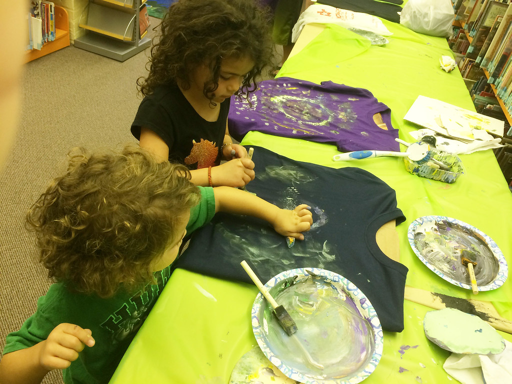 . Vincenzo, 3, and Serafina, 5, Yaghooty of Blue Bell paint their shirts during Pottstown Library\'s Galaxy Painting Party Friday. Photo by Evan Brandt - Digital First Media