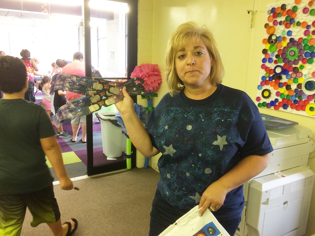 . Lisa Kraljevich, Children\'s Director at Pottstown Regional Public Library, holds up the solar eclipse viewing glasses that were given out during Pottstown Library\'s Galaxy Painting Party Friday. Photo by Evan Brandt - Digital First Media