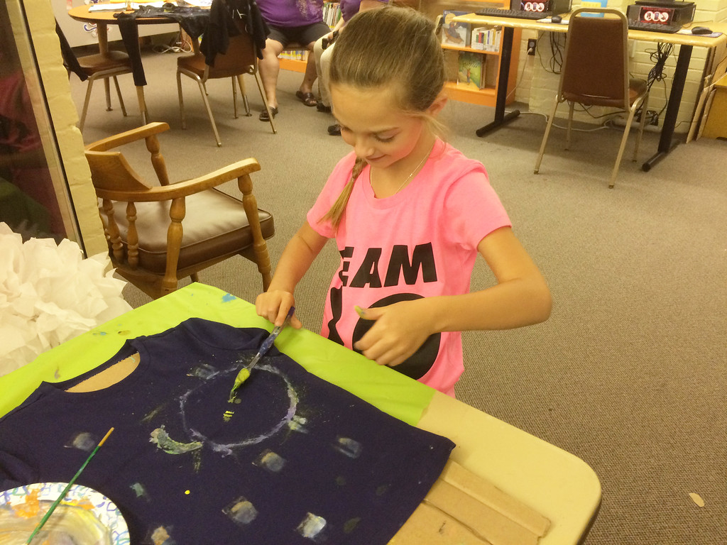 . Scarlette Shaner, 7, of Boyertown carefully paints a shirt during Pottstown Library\'s Galaxy Painting Party Friday. Photo by Evan Brandt - Digital First Media