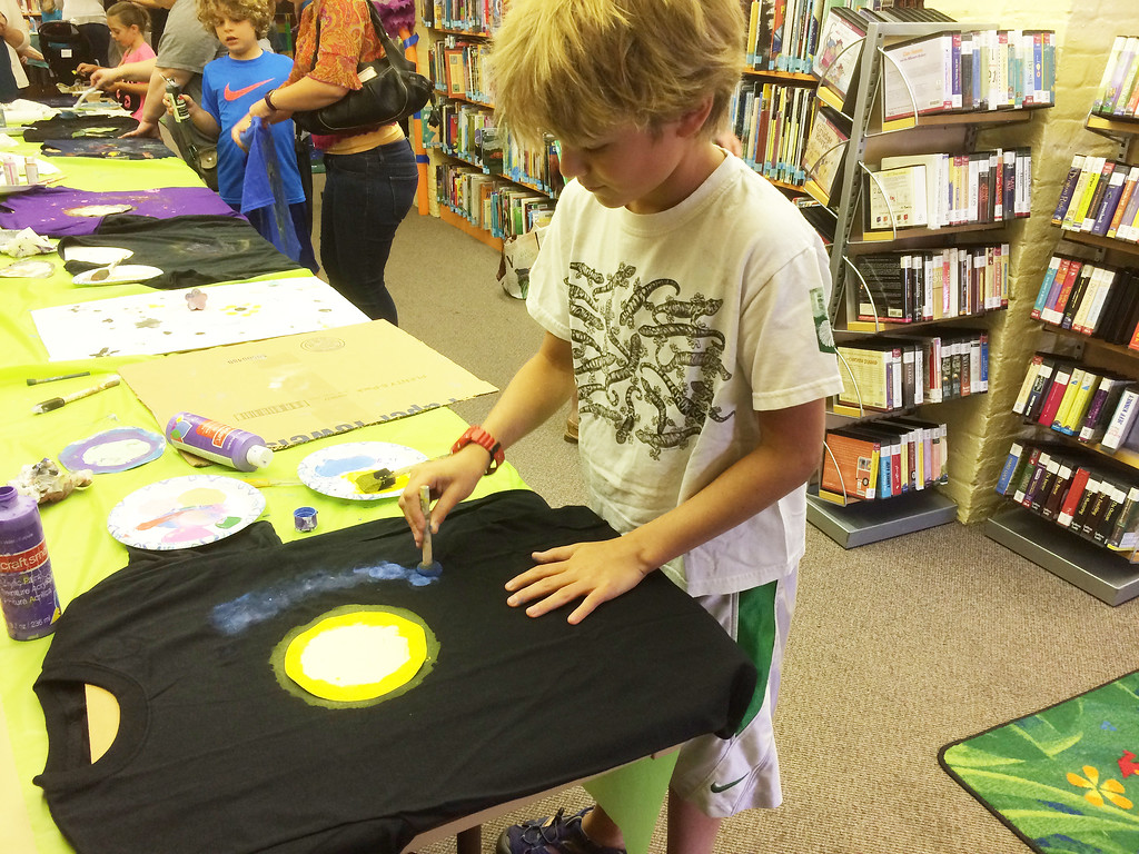 . Chase Bartolini, 11, of North Coventry takes extra care while painting a shirt at Pottstown Library\'s Galaxy Painting Party Friday. Photo by Evan Brandt - Digital First Media