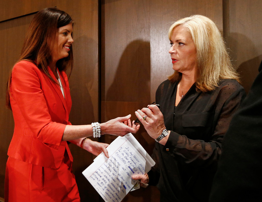 . Pennsylvania Attorney General Kathleen G. Kane, left, hands her notes to an aide after her news conference in Scranton, Pa., Tuesday, Feb. 16, 2016. Kane said she will not seek a second term, facing pressure from within her own party after being hobbled for months by criminal perjury charges and the suspension of her law license. (AP Photo/Rich Schultz)