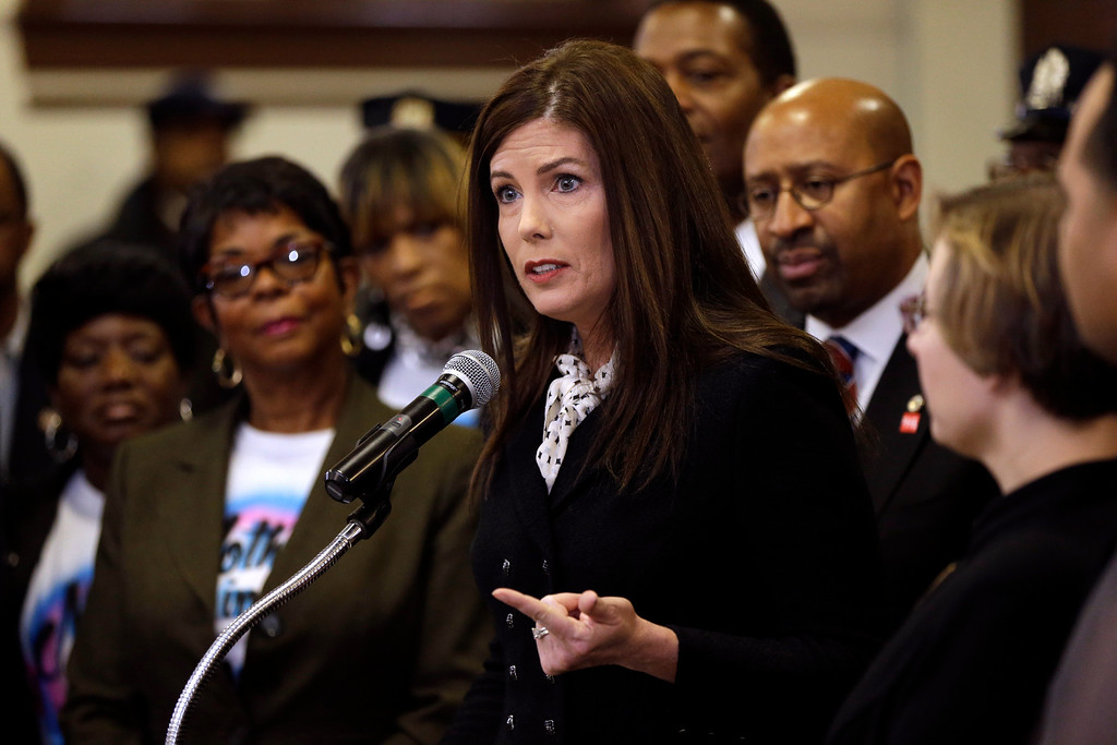 . Pennsylvania Attorney Gen. Kathleen Kane, accompanied by Philadelphia Mayor Michael Nutter, center right, community members, and elected officials, speaks during a news conference Friday, Feb. 8, 2013, in Philadelphia as she announces that Pennsylvania officials are closing a gun-law loophole that lets residents get permits online from Florida, sometimes when they can\'t get them at home. (AP Photo/Matt Rourke)