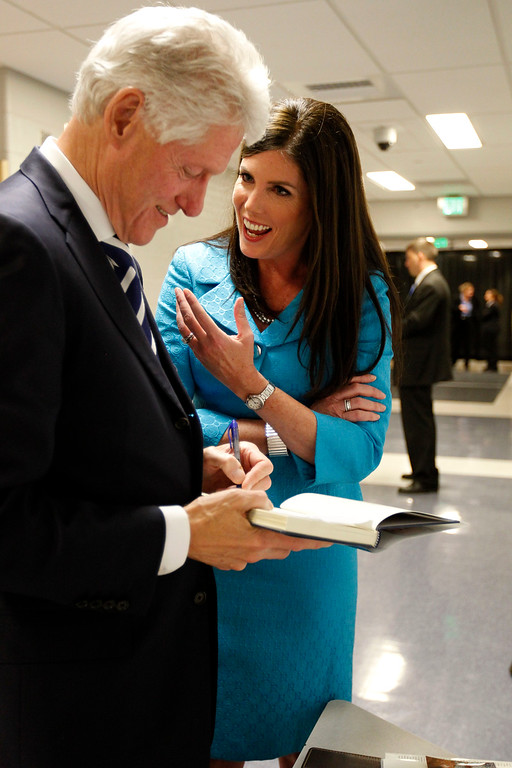 . President Bill Clinton, left, autographs items as Kathleen Kane, right, a democratic candidate for Pennsylvania Attorney General, speaks at Upper Moreland High School Thursday, April 12, 2012 in Willow Grove, Pa. President Clinton spoke earlier at an event to endorse Kane. (AP Photo/Alex Brandon)