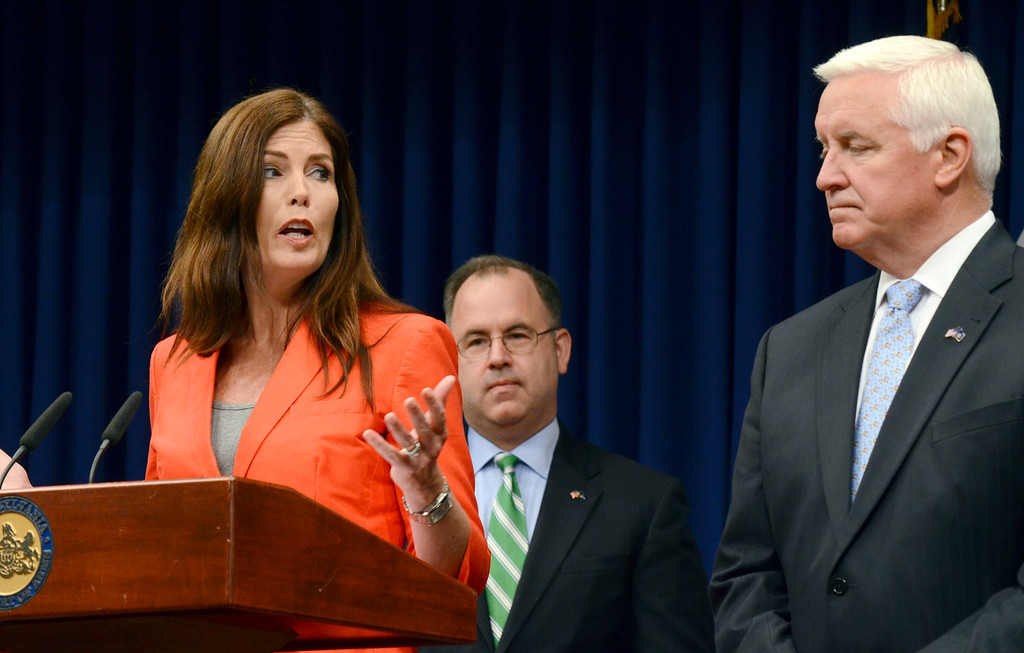 . Attorney General Kathleen Kane gestures to Gov. Tom Corbett while speaking at a news conference Friday, June 27, 2014, at the Capitol in Harrisburg, Pa. Corbett and Kane announced details of an agreement to allow some Highmark insurance enrollees under certain conditions to continue using its doctors and facilities at in-network rates under a consent decree filed in court Friday, after a long and bitter fight between the two western Pennsylvania health care giants. (AP Photo/Marc Levy)