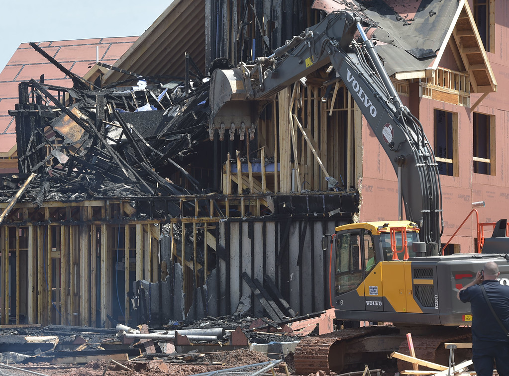 . PETE  BANNAN-DIGITAL FIRST MEDIA         A excavator was brought in to demolish sections of the townhouse damaged by a  fire in the 700 block of Wheatland Street in Phoenixville. The new development is just off Mason Street.
