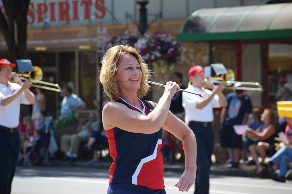 . Members of the Boyertown Alumni Marching Band twirl their batons in celebration as they march and dance down High Street Tuesday for the Fourth of July Parade in Pottstown.--Marian Dennis, Digital First Media
