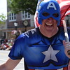 A parade participant dressed as Captain America high-fives guests as he runs down High Street during the Fourth of July parade Tuesday.--Marian Dennis, Digital First Media