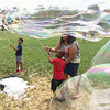 Evan Brandt — Digital First Media<br /> With a little help, Keem Hill, 4, of Pottstown, in the red shirt, gets the knack for giant bubble making during the GoFourth! Festival in Pottstown's Memorial Park Wednesday.