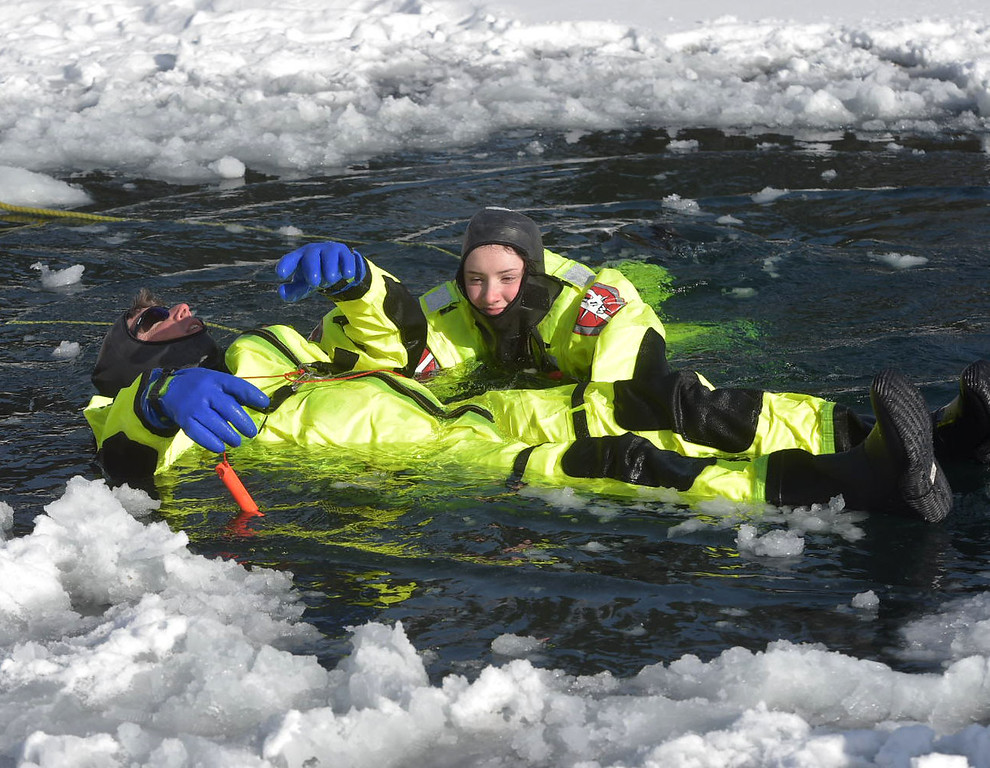 . PETE BANNAN-DIGITAL FIRST MEDIA   Firefighter Nicole McCarthy practices rolling her father, firefighter Mark McCarthy onto the ice shelf.during training at North Hills pond.
