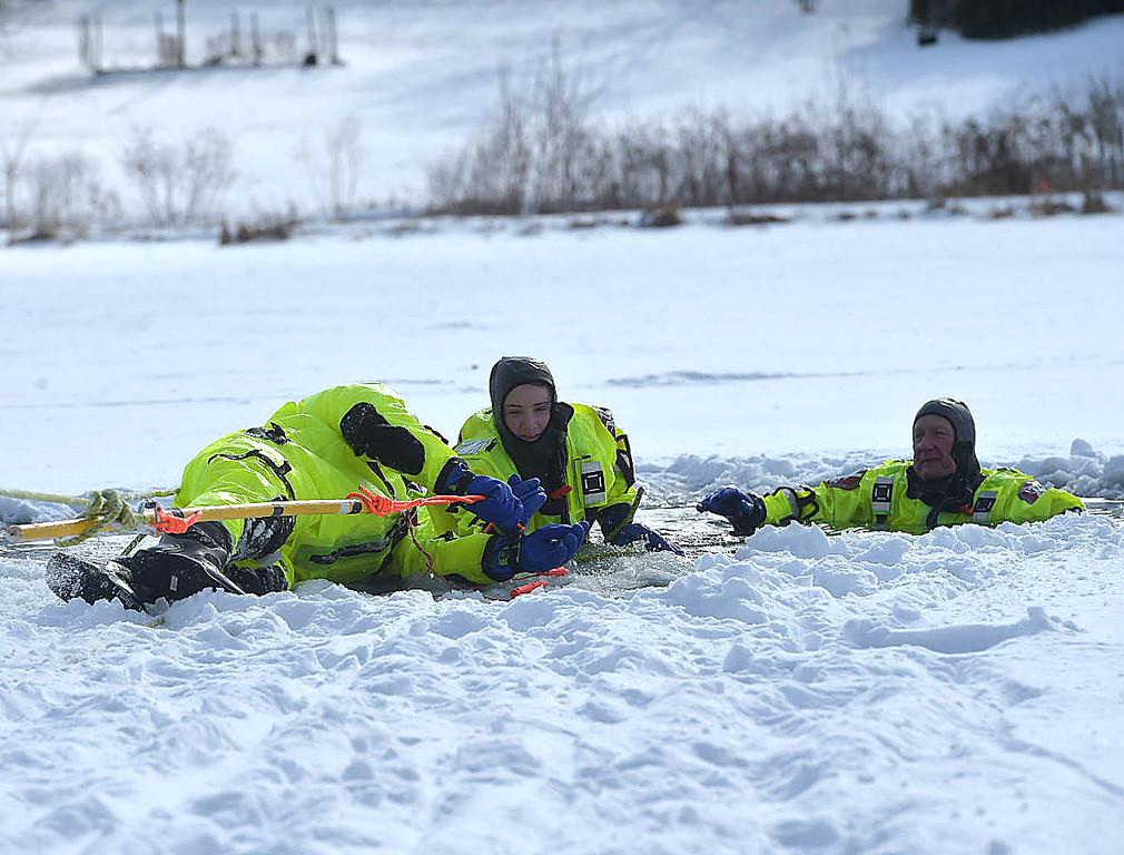 . PETE BANNAN-DIGITAL FIRST MEDIA   Firefighter Pat Dixon pulls \'victim\' Nicole McCarthy onto the ice shelf during training at North Hills pond.