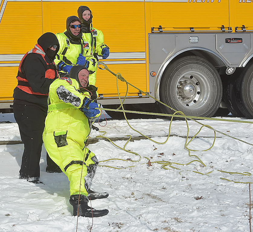 . PETE BANNAN-DIGITAL FIRST MEDIA   Fame firefighters pulls a \'victim\' off the ice during training at North Hills pond.