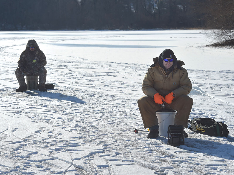 "PETE BANNAN -DIGITAL FIRST MEDIA     John  and Matthew Young ice fishing at Marsh Creek State Park Tuesday.  ""I haven't caught anything, you should talk to John, he has three,"" joked Matthew who now lives in Emanus. "" It's nice being out. The ice can vary the best is clean black ice four inches thick.  This ice is about 4-5 inches thick."""