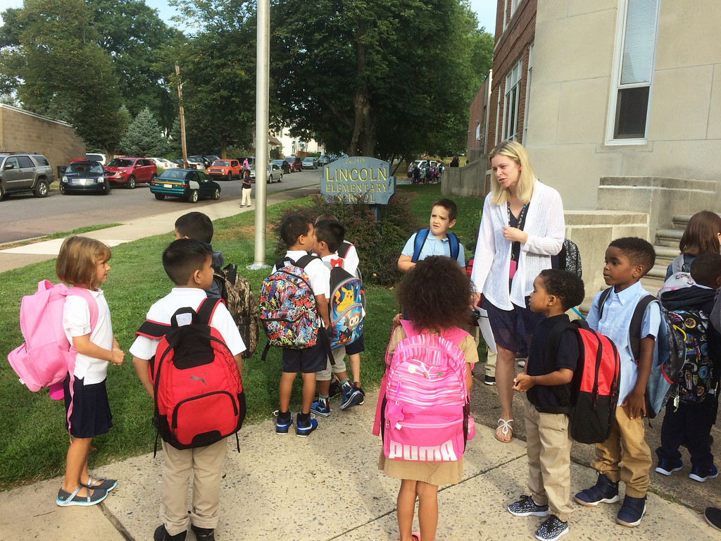 . Intervention assistant Gerauldine Alderfer greets students out front of the Lincoln Elementary on the first day of school Monday. Evan Brandt -- Digital First Media