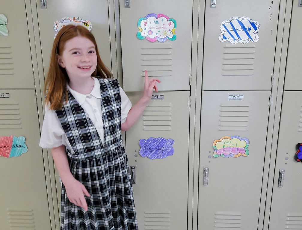 . Student Julia Ross shows off her new locker during her first day back at St. Aloysius Parish School Monday.