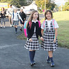 Two friends hold hands with excitement as they make their way down the car line into the new St. Aloysious Parish School building in the former St. Pius X High School.