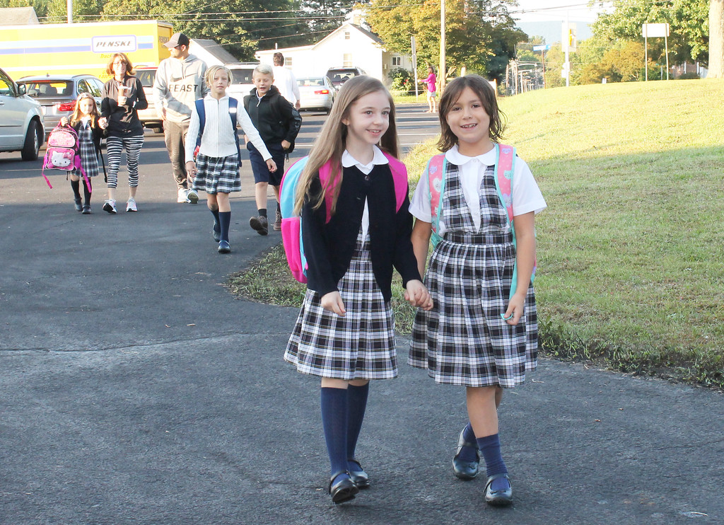 . Two friends hold hands with excitement as they make their way down the car line into the new St. Aloysious Parish School building in the former St. Pius X High School.