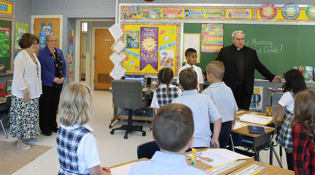 . The Rev. Joseph Maloney, pastor of St. Aloysius Parish, talks with students on the school\'s first day in the new building, the former St. Pius X High School in Lower Pottsgrove.