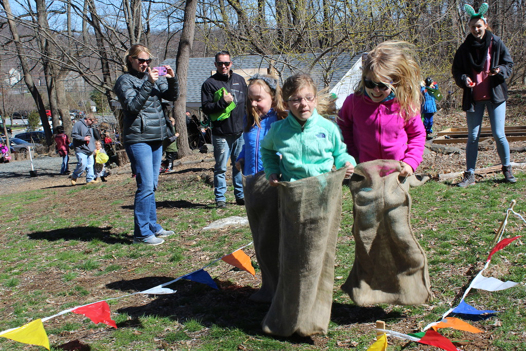 . Three girls run in a sack race at the Atlhouse Arboretum in Upper Pottsgrove on Saturday. The arboretum held a forest egg hunt for children then the kids were able to enjoy several fun activies after they collected their eggs.