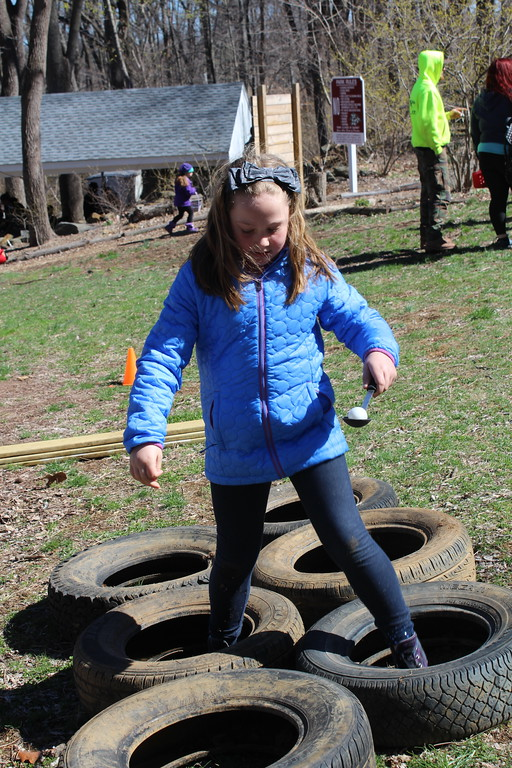 . Grace Druckenmiller, 7, walks through tires during an egg race at the Althouse Arboretum in Upper Pottsgrove on Saturday. Families were able to explore forest trail during an Easter egg hunt then they enjoyed fun activities afterward.