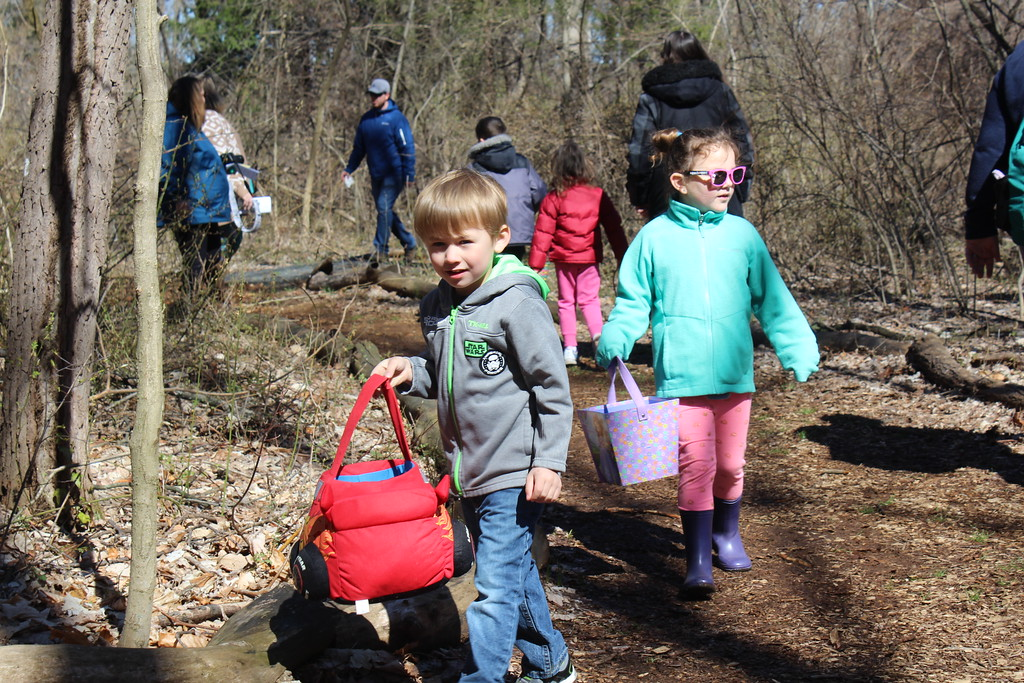 . Landon Wheeles, 5, and Emma Allen, 6, carry colorful baskets while searching for hidden plastic eggs along forest trails of the Althouse Arboretum on Saturday, April 8, 2017.