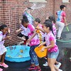 Students have some water fun while getting sprayed with a hose during a field day event at Franklin Elementary School in Pottstown Friday, May 27, 2015.