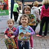 Alora Knapper, 3, stands in front of siblings Murphy, 1, and Lily,5, while all three hold books they received for free from the Federation of Pottstown Teachers during the first outdoor Pottstown farmers market.