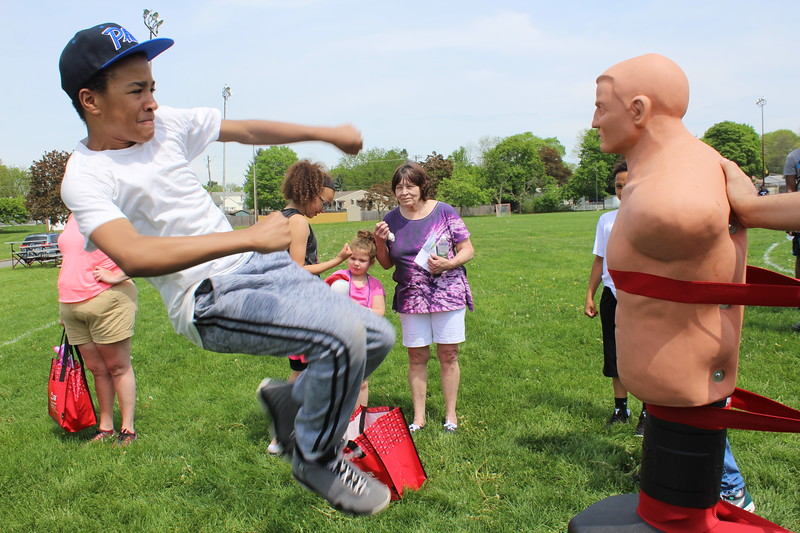 Radee Murray, 13, does a kicking move on a mannequin during a celebration for families at Pottstown High School on Saturday. Murray is a student at Red Cloud Kung Fu of Pottstown