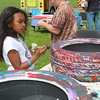 A young girl paints a car tire as part of a Pottstown Community Arts project. The tires will be spread throughout the community then filled with dirt and flowers.