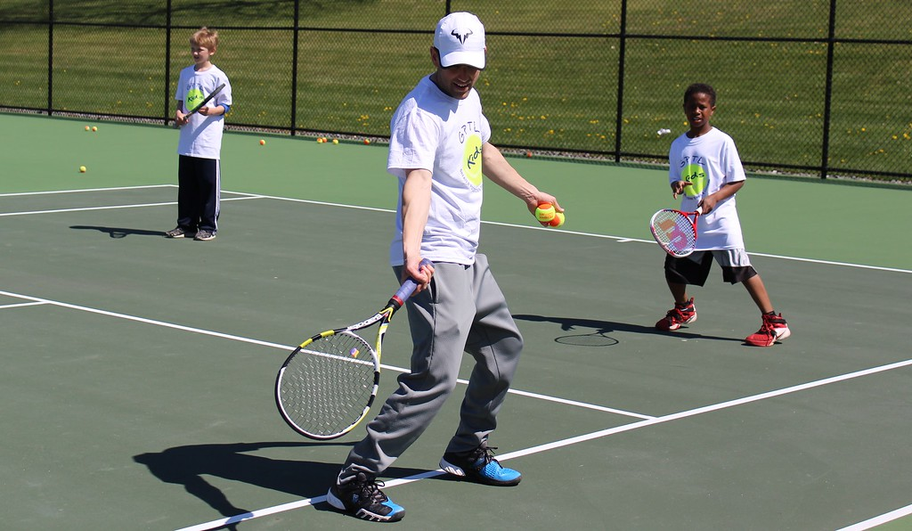 . Michilea Patterson, Digital First Media Greater Pottstown Tennis & Learning instructor Chris Herdelin teaches children some basics of the sport during the combined PEAK Pottstown Celebrates Young Children and YMCA Healthy Kids Day event Saturday.