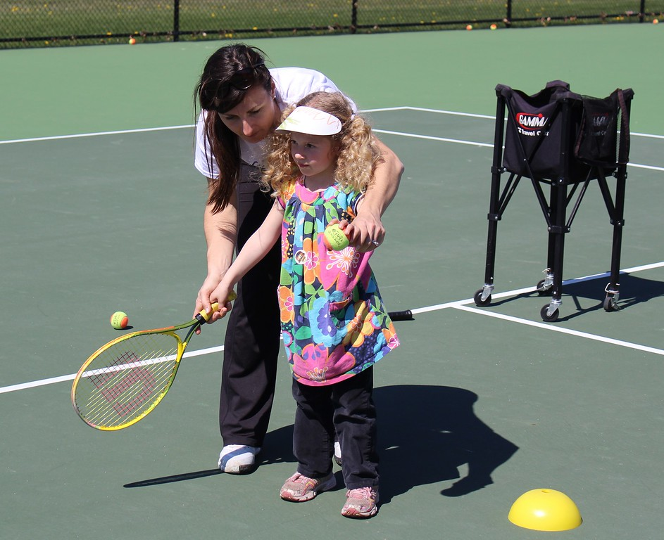 . Michilea Patterson, Digital First Media  An instructor shows Danielle Bechtel, 4,  how to hold a tennis racket during a free clinic at a celebration of children in Pottstown.
