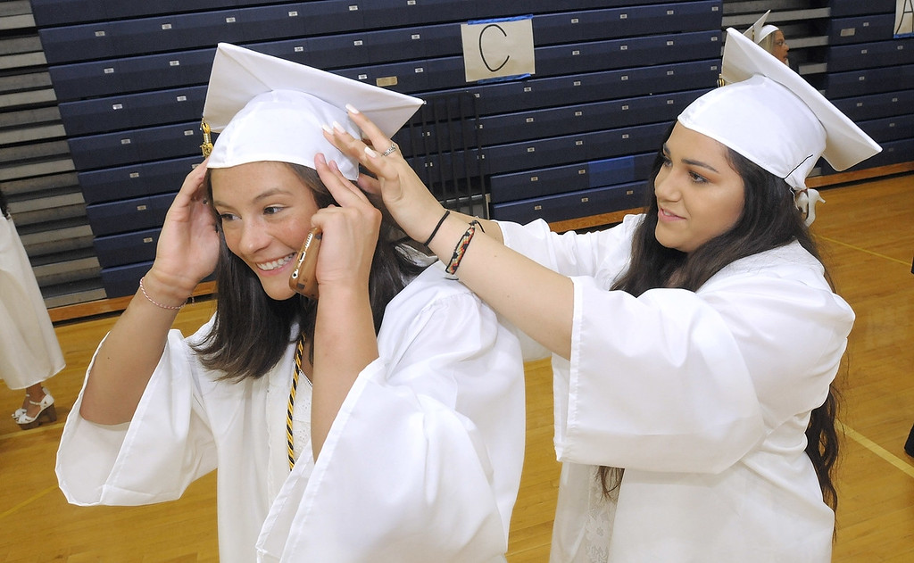 . Gene Walsh � Digital First Media Alyssa Palmucci helps Hailey Lai with the cap before the start of Spring Ford graduation June 13, 2018.